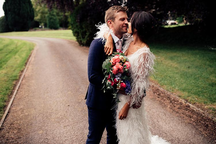 Groom in Blue Check Suit Embracing His Bride in a Feather Wedding Dress