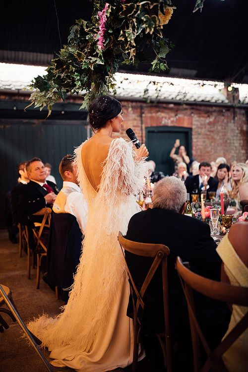 Bride in Wedding Dress with Feathers Delivering Her Wedding Speech