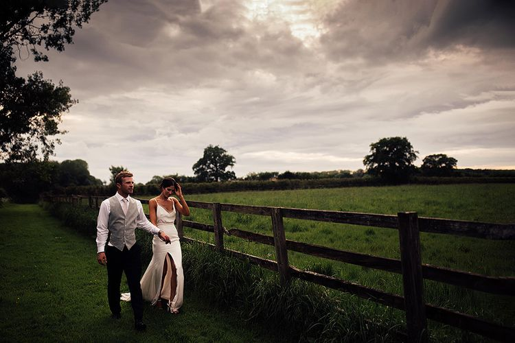 Bride and Groom Strolling Through a Field