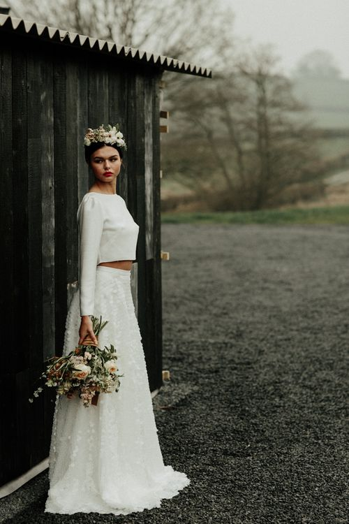 Stylish bride in sequin skirt and bridal crop top with flower crown and bouquet