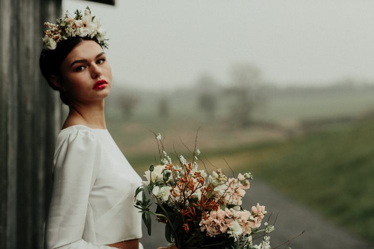 Beautiful bride with red lipstick holding an earthy bouquet in a bridal crop top