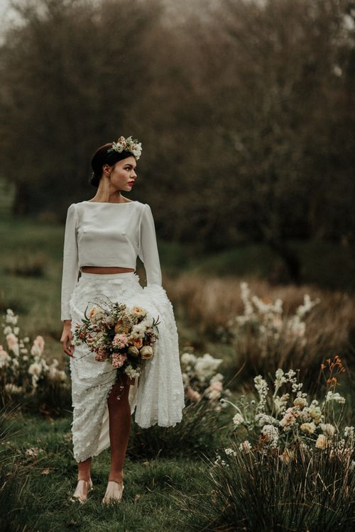 Boho bride in satin bridal crop top and sequin bridal skirt in a field