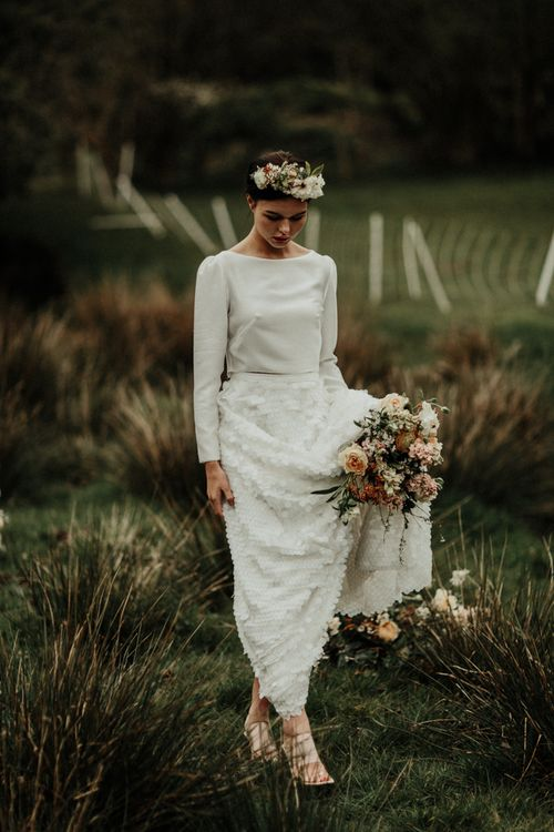 Bride in bridal crop top holding her bouquet and skirt in a field