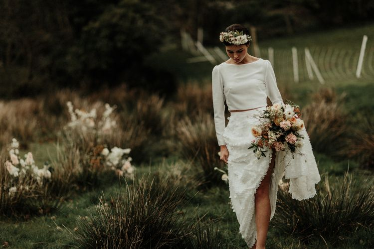 Boho bride in flower down sequin skirt and bridal crop top walking in the Welsh countryside
