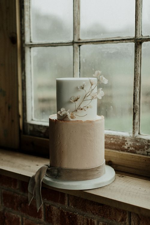 Pink and white wedding cake with delicate flower decor and velvet ribbon