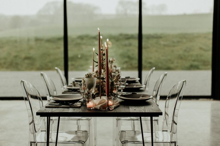 Elegant tablescape with coloured taper candles and ghost chairs