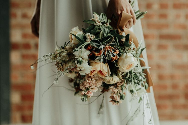 Muted flower wedding bouquet tied with ribbon and bridal crop top