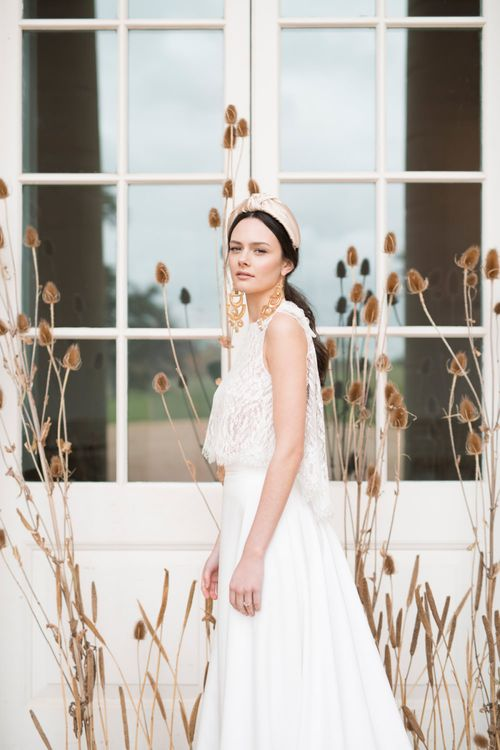 Bride in Jesus Peiro Wedding Dress with Turband Headband and Statement Gold Earrings