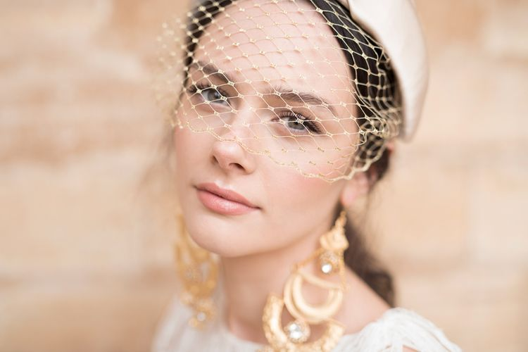 Beautiful Bride with Natural Makeup and On-Trend Turban Headband with birdcage Veil and Statement Gold Earrings