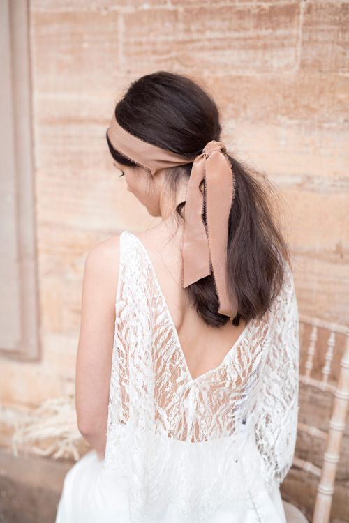 Bride in Lace Back Jesus Peiro Wedding Dress and Sleek Pony Tale Hairstyle with Ribbon