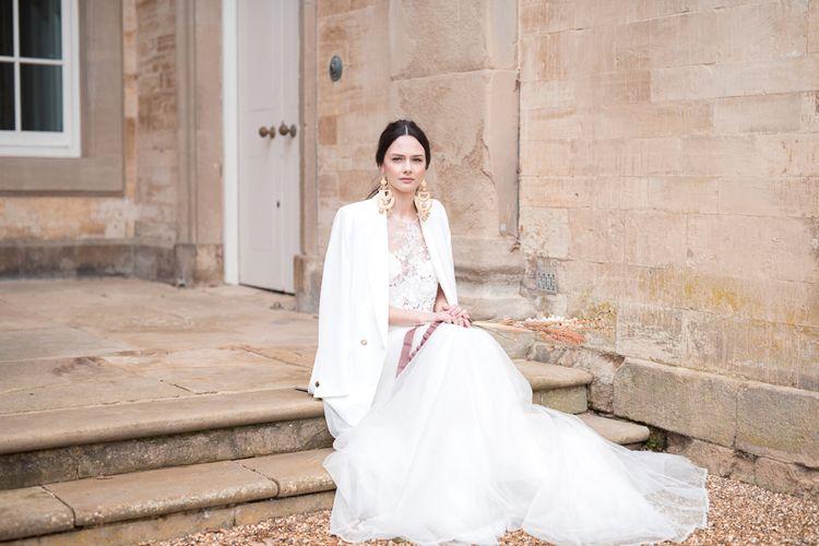 Stylish Bride in Jesus Peiro Wedding Dress with White Jacket, Sleek Back Hair & Statement Gold Earrings