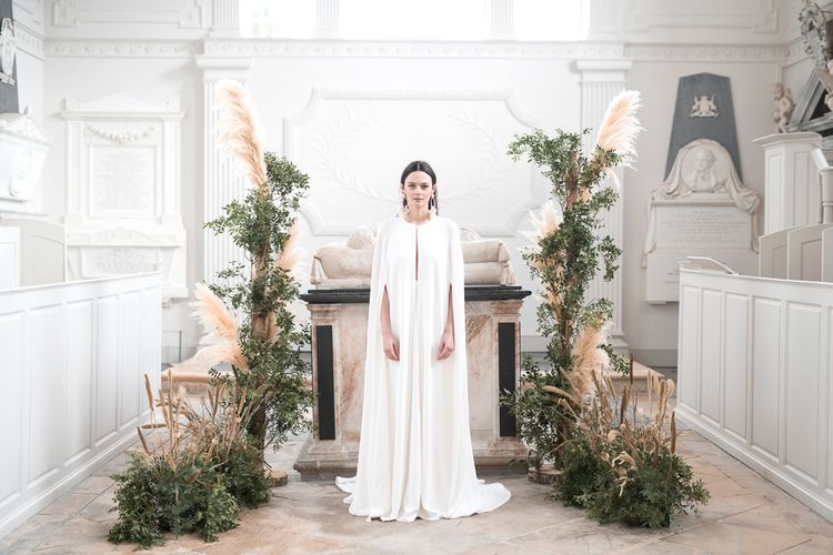 Bride in Jesus Peiro Wedding Dress and Bridal Cape Standing in Front of a Floral installation of Pampas Grass and Dried Flowers