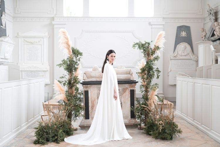 Bride in Plain Bridal Cape Standing in Front of a Floral installation of Pampas Grass and Dried Flowers