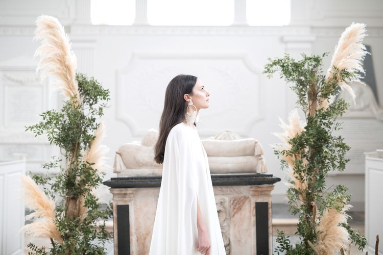 Bride Wearing Statement Earrings and Plain Bridal Cape Standing in Next to  Floral Installation of Pampas Grass and Dried Flowers