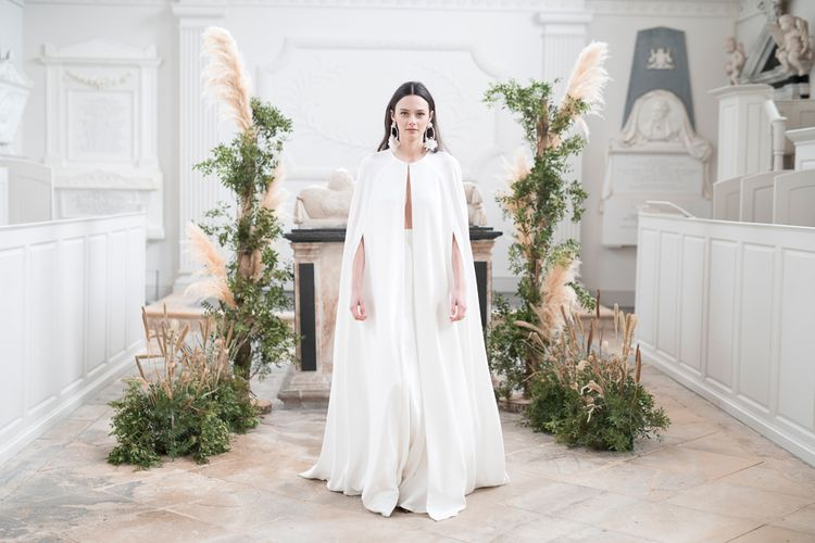 Stylish Bride in Jesus Peiro Wedding Dress and Bridal Cape Standing in Next to a Floral installation of Pampas Grass and Dried Flowers