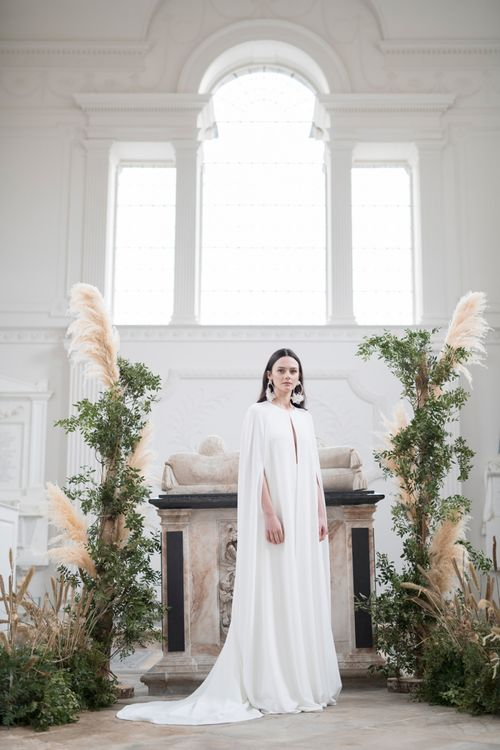 Stylish Bride in Jesus Peiro Plain Bridal Cape Standing in Next to a Floral installation of Pampas Grass and Dried Flowers