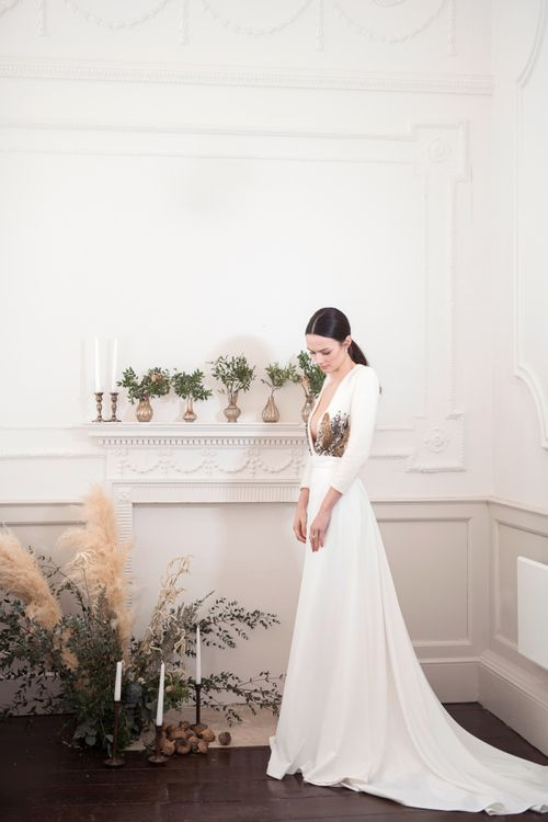 Bride in Jesus Peiro Wedding Dress with Plunging Neckline Standing Next to a Fireplace