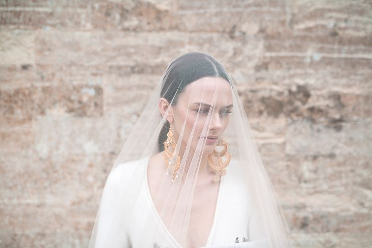Bride in Sheer Bridal Veil Showing off Statement Earrings and Sleek Hairstyle