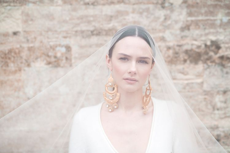 Beautiful Bride with Natural Makeup in Sheer Bridal Veil Showing off Statement Earrings and Sleek Hairstyle