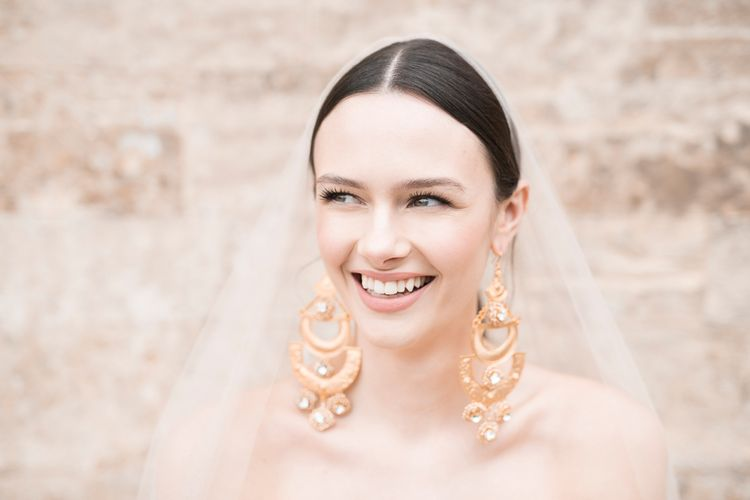 Smiling Bride with Natural Makeup & Sleek Wedding Hair Showing off Statement Earring
