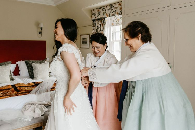 Mother of the bride and groom helping the bride into her wedding dress