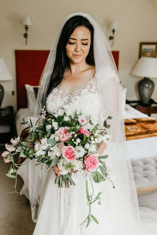 Bride in lace and tulle wedding dress golding a pink and white wedding bouquet