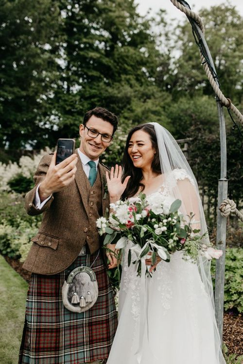 Bride and groom face timing guests after their socially distanced wedding ceremony