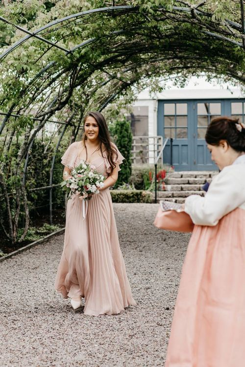 Bridesmaids in dusky pink dress walking down the aisle