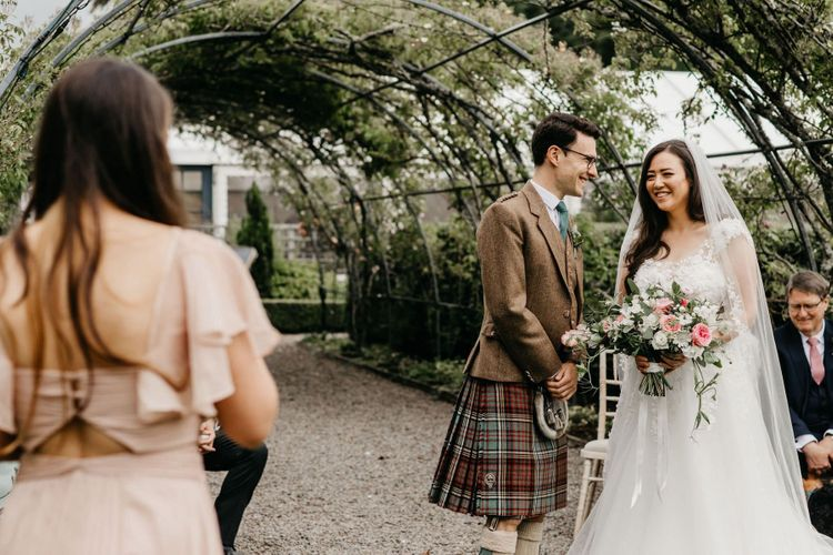 Bride in lace and tulle wedding dress and Groom in Tartan kilt at socially distanced wedding