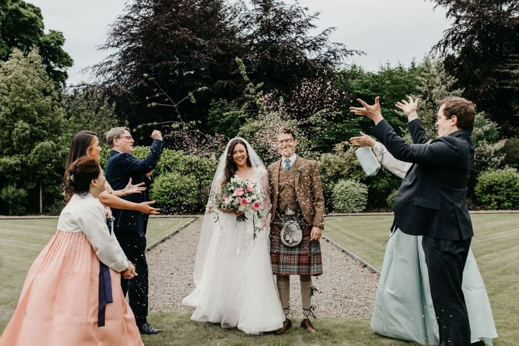 Confetti moment with bride in lace and tulle dress, groom in tartan kilt and parents in Hanboks - Korean wedding dress