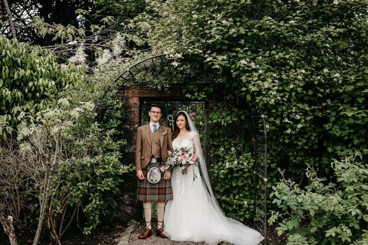 Bride in lace and tulle wedding dress and groom in tartan kilt at micro