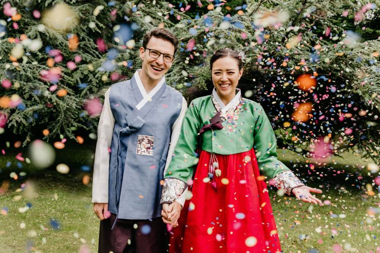 Confetti moment at multicultural wedding with tailor made Hanboks Korean wedding dress outfits