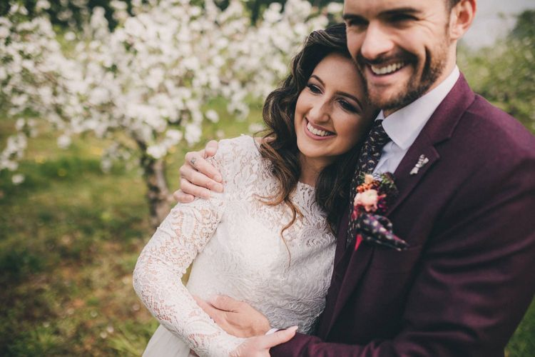 Groom in Burgundy Suit and Bride in Lace Wedding Dress Embracing