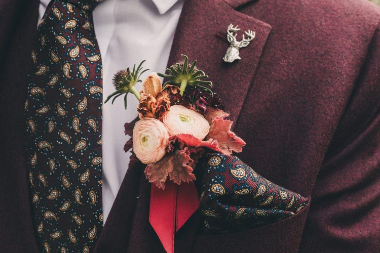 Groom in Burgundy Wool Suit with Deep Floral Buttonhole