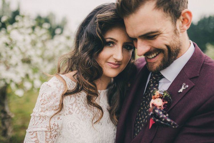 Groom in Burgundy Suit and Bride in Lace Wedding Dress Embracing in an Orchard