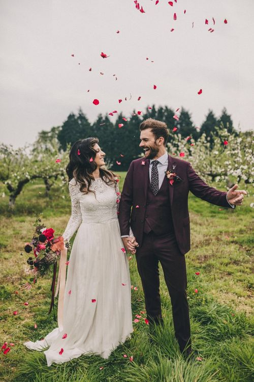 Red Confetti Moment with Bride in Lace Wedding Dress and Groom in Burgundy Suit
