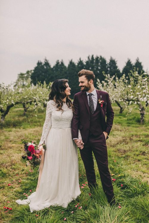 Bride in Lace Wedding Dress and Groom in Burgundy Suit Holding Hands in an Orchard