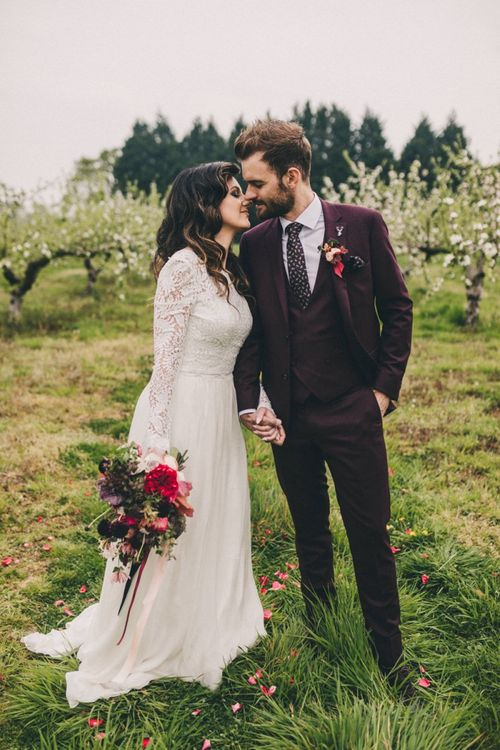 Bride in Lace Wedding Dress and Groom in Burgundy Suit Kissing in an Orchard