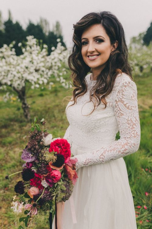 Beautiful Bride in Lace Wedding Dress Holding a Vibrant Burgundy, Red and Pink Wedding Bouquet