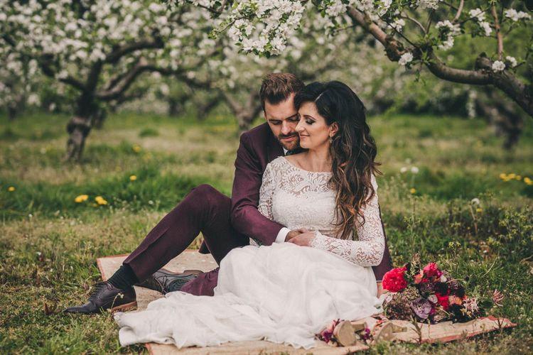 Bride and Groom Embracing on a Rug in an Orchard