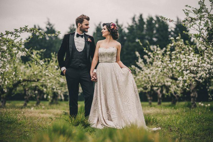 Black Tie Wedding Attire with Groom in Tuxedo and Bride in Sweetheart Neckline Wedding Dress with Geometric Pattern