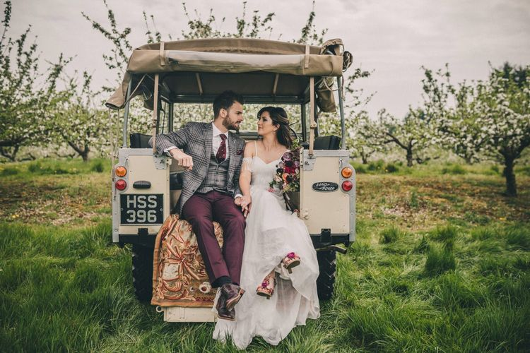 Bride and Groom Sitting on the Back of Land Rover
