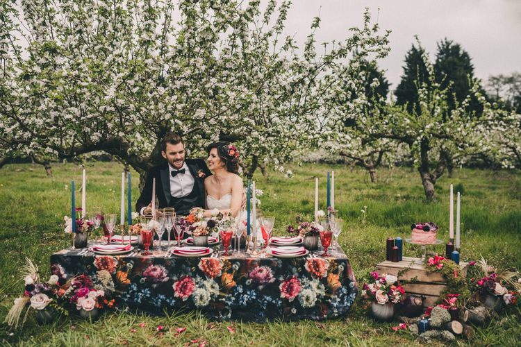 Elegant Bride and Groom Sitting at a Vibrant Floral Tablescape