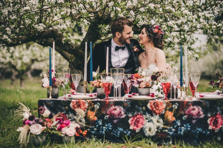 Bride and Groom Sitting at Their Outdoor Wedding Breakfast Table