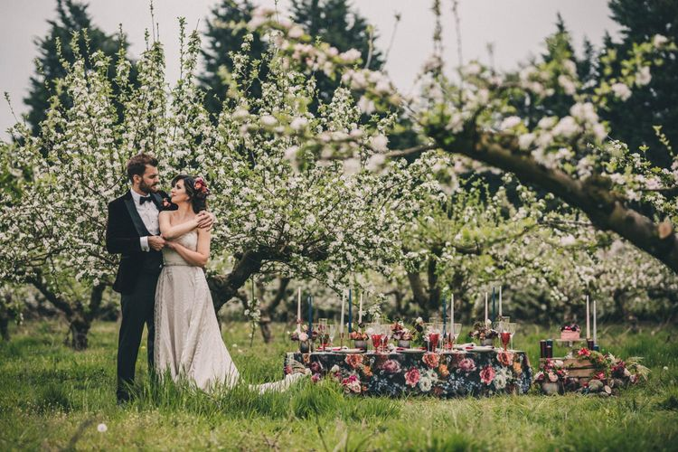 Groom in Black Tie Suit and Bride in Off the Shoulder Dress Standing in an Orchard