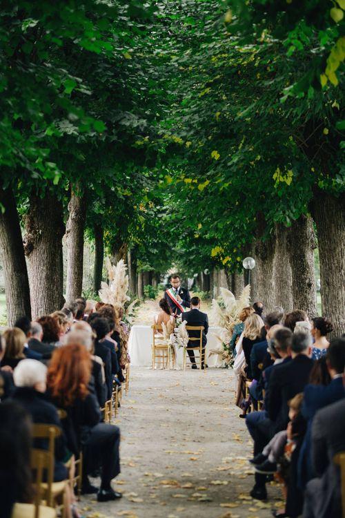 Outdoor Wedding Ceremony | Bride in Silk Jenny Packham Gown | Groom in Navy Blue Suit | Glamorous, Roaring Twenties, Great Gatsby Inspired Wedding at Villa Borromeo  in Italy | Matrimoni all'Italiana Photography