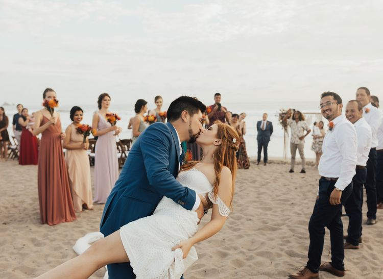 Groom Kisses Bride on Beach After Ceremony