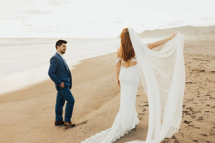 Bride Holds Up Veil On Beach With Groom In Navy Suit