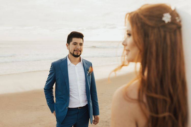 Groom In Navy Suit with Orange Buttonhole and Bride with Floral Hair Accessories