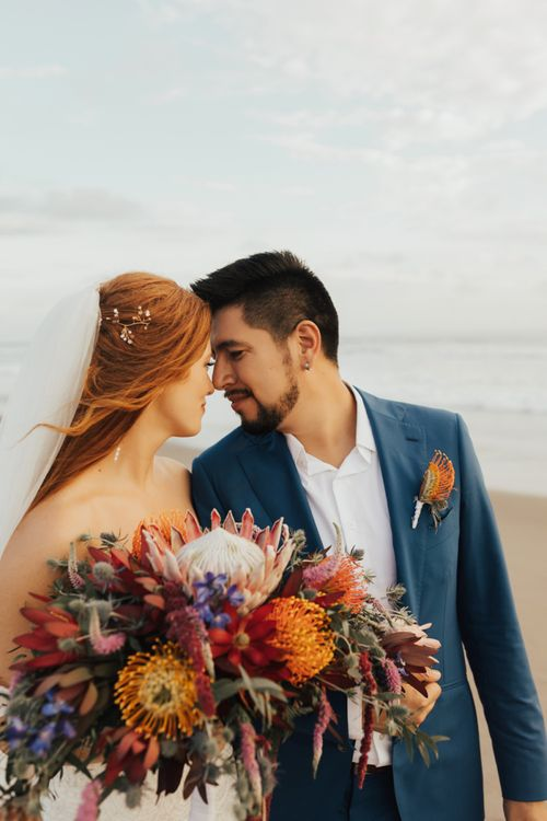 Bride and Groom After Ceremony With Veil and Navy Suit